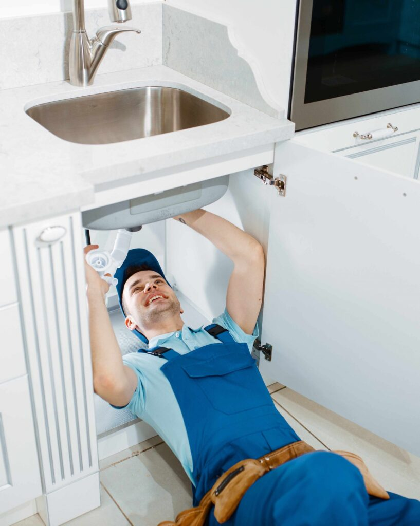 male-plumber-in-uniform-installing-drain-pipe-JF85MSE-scaled.jpg