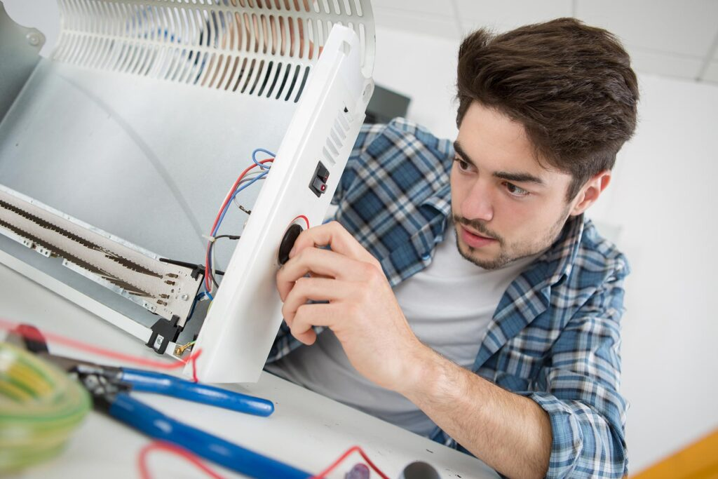 young-male-plumber-examining-electric-heater-PLXD3ZH.jpg